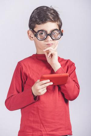 nerdy: Funny nerdy little boy holding a smart phone