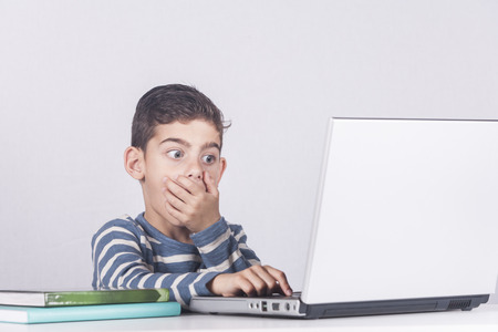 Young boy reacts while using a laptop. Internet safety for kids concept Standard-Bild