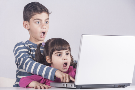 Scared little kids react while using a laptop. Internet safety for kids concept