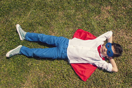 unbeatable: Little superhero lying on the grass. Toned image with selective focus