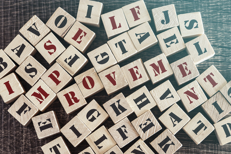 Self Improvement message formed with wooden blocks. Cross processed image