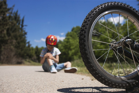 Boy is lying hurt after a bicycle accident. Kids safety concept. Selective focus image with shallow depth of field Archivio Fotografico