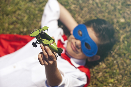 unstoppable: Little superhero lying on the grass holding an airplane