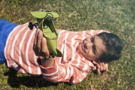 Boy holding a toy airplane lying on the grass Stock Photo