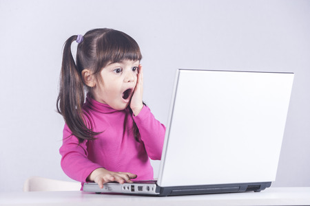 Cute little girl reacts with shock while using a laptop. Internet safety concept Standard-Bild
