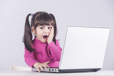 Cute little girl reacts with shock while using a laptop. Internet safety concept Stock Photo