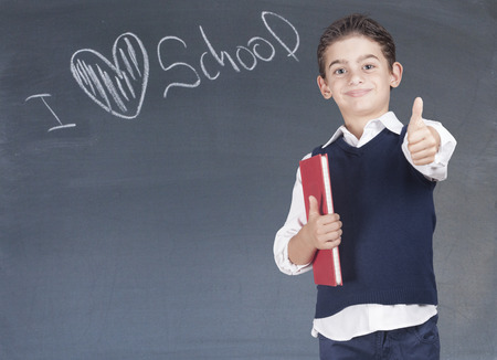 feelings and emotions: First day of school. Confident little school boy in front of a blackboard