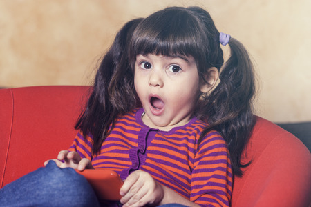 reacts: Little girl reacts while being caught using a smartphone.