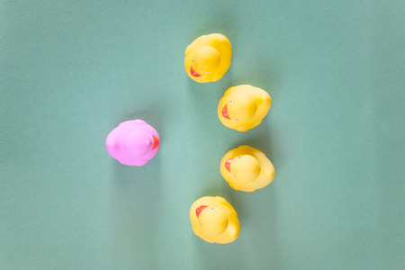 Discrimination and social exclusion concept with different color rubber ducks