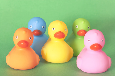 Diversity concept. Group of different color rubber ducks. Retro toned image with selective focus