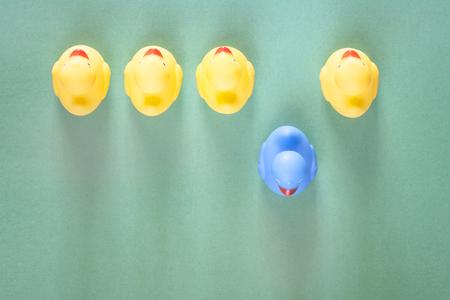 racismo: pato de goma azul que se coloca hacia fuera de las amarillas comunes. Singularidad, la diferencia, la individualidad y sobresaliendo de la multitud concepto