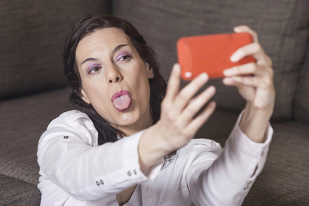 mocking: Woman making a mocking gesture while taking a selfie Stock Photo