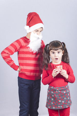 Little girl holding her Christmas present while her Santa dressed brother reacts Stock Photo