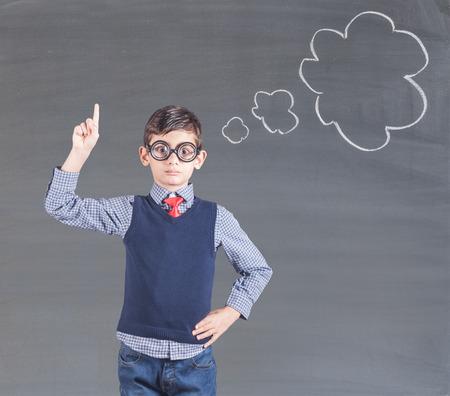 Smart little boy in front of a blackboard