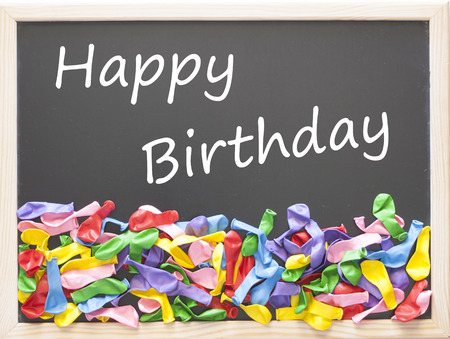 deflated: Happy Birthday card with colorful deflated balloons on a blackboard Stock Photo