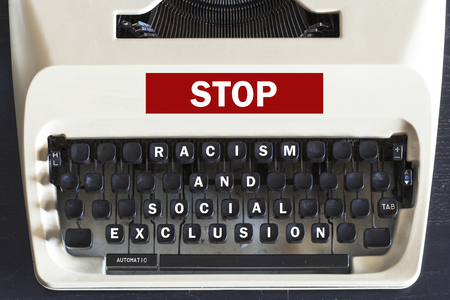 exclusion: Retro typewriter with stop racism and social exclusion message written on it