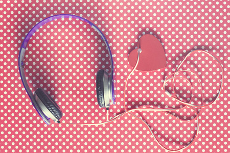 background texture metaphor: Love music concept with headphones and red heart on vintage polka dots background. Table top view