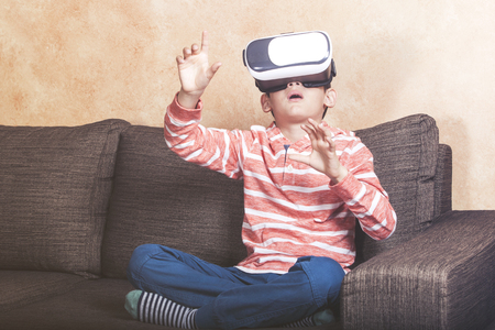 Astonished little boy using virtual reality headset at home 免版税图像