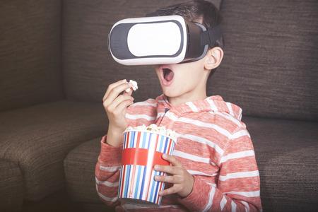 Verbaasde kleine jongen met behulp van virtual reality headset thuis Stockfoto