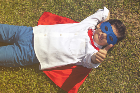unstoppable: Confident little superhero lying on the grass showing thumbs up Stock Photo