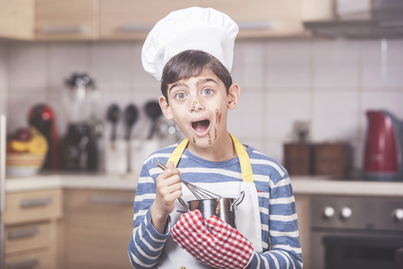pretending: Young boy chef with chocolate on his face Stock Photo