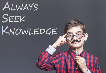 seeking: Funny little genius school boy with Always Seek Knowledge quote. Education concept Stock Photo