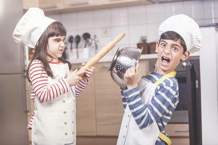 Enfants habillés comme chefs qui se battent dans la cuisine Banque d'images - 80935933