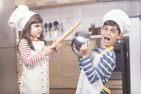 Kids dressed as chefs fighting in the kitchen