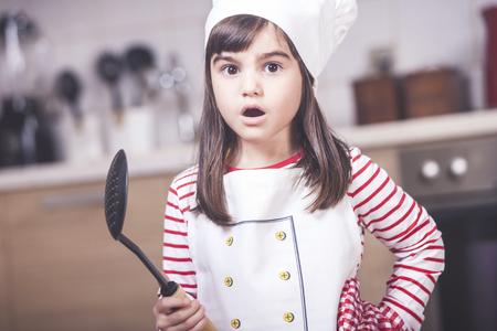 niños actuando: Cute little girl chef in the kitchen