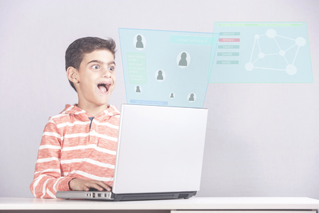 Excited young boy using his laptop to connect with friends