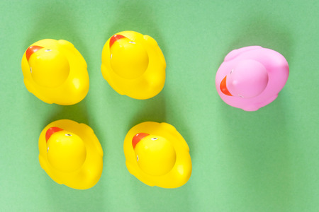 Racism, homophobia, discrimination and social exclusion concept with a pink rubber duck standing out from the common yellow ones Stock Photo