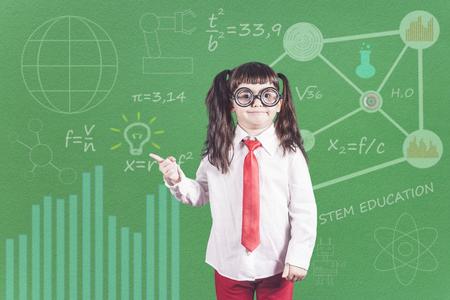 Concept de l'éducation avec drôle petite écolière génie devant un tableau Banque d'images - 87985340