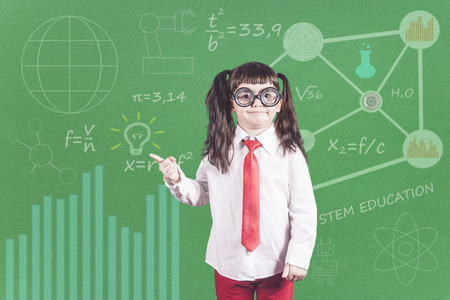 Education concept with funny little genius school girl in front of a chalkboard Stock Photo