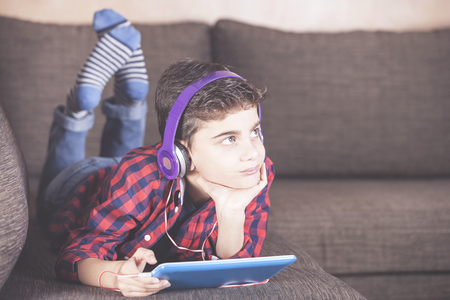 Trendy boy listening to his favorite music using his tablet Stock Photo