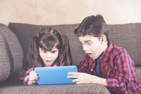 Shocked little kids react while watching inappropriate content on their tablet. Internet safety for kids concept