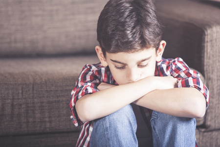 Sad kid lost in his thoughts. Depression concept Stock Photo