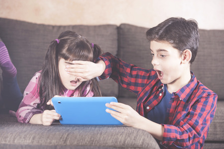 Little boy protects his sister from watching inappropriate content while using a tablet. Internet safety for kids concept