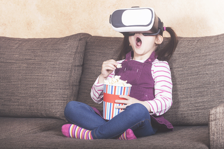 Excited little girl experiencing virtual reality at home