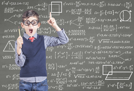 Education concept with funny school boy in front of a chalkboard full of equations Stock Photo
