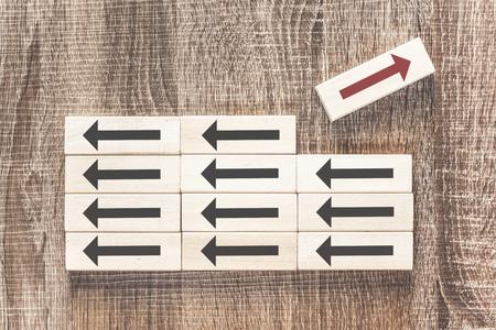 Unicité, différence, individualité et se démarquer du concept de foule avec une flèche rouge pointant à l'opposé des noirs