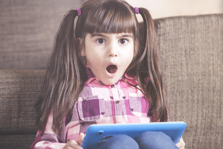 Shocked little girl reacts while watching inappropriate content on her tablet. Internet safety for kids concept Stock fotó