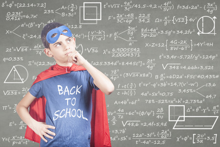 Back to school concept with super hero school kid thinking hard in front of a blackboard Stock Photo