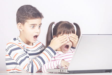 Little boy protects his sister from watching inappropriate content while using a computer. Internet safety for kids concept 版權商用圖片