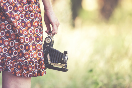 Young woman holding a vintage camera outdoors. Nostalgia concept
