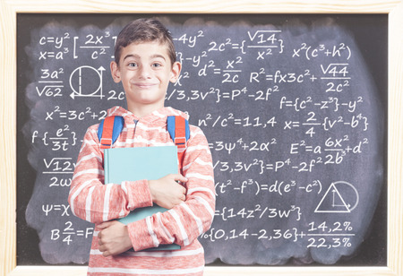 Education concept with happy school boy in front of a blackboard Stock Photo