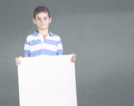 Boy holding a white cardboard with copy space Stock Photo - 112521809