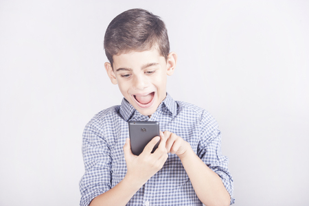 Trendy young boy using his smart phone. Kids and mobile technology concept Stock Photo - 112521814