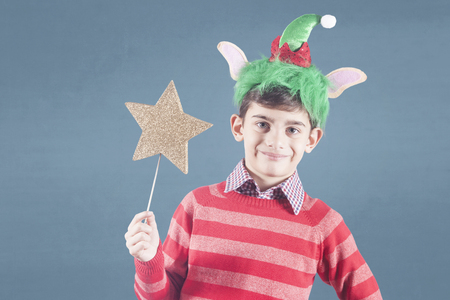 Boy full of Christmas spirit wearing a reindeer hat holding a golden star with copy space