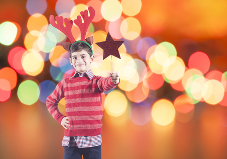 Boy full of Christmas spirit with elf hat holding a red star with copy space Stock Photo - 112521850