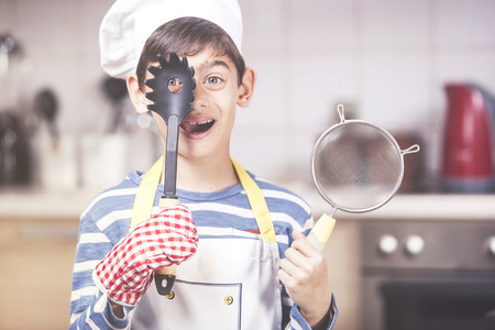 Cute little boy chef posing in the kitchen
